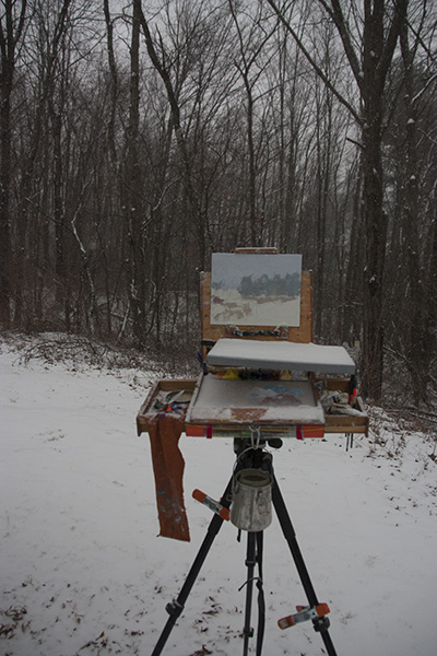 Pochade box on tripod in snowstorm with painting in progress. Palette area partially sheltered from snow by wood and plexiglass panel clamped above it.