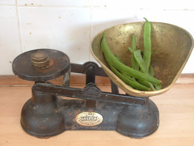 An oldfashioned set of baking scales, with fresh runner beans in the weighing bowl