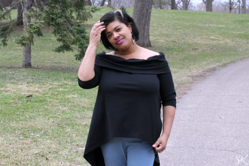 a woman wearing a black off the shoulder shirt outside