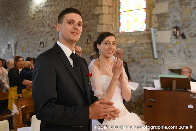 portrait des mariés qui applaudissent dans l'église