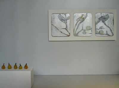 Modern miniature gallery space with five felted pears displayed on a plinth, and a triptych on the wall.