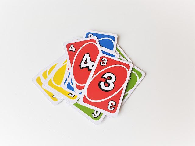 na zdjęciu stos kart odkrytych, na wierzchu karta czerwona trójka