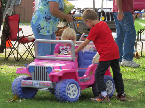 kids driving a battery powered jeep