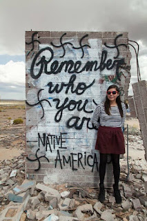 "Amber on the rez in front of graffiti reading ""Remember who you are: Native America"""
