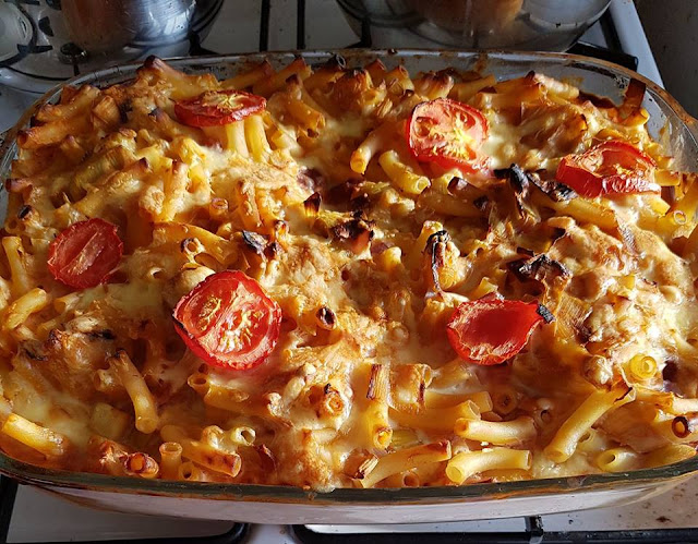 An oven dish filled with very cheesy macaroni, browned on top and topped with tomato slices