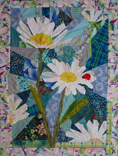Bright red ladybug rests on the white petal of a daisy in this original art quilt.