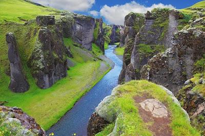 Paisaje de Islandia, donde un río cruza un valle de precipicios escarpados, con mucha hierba verde y un cielo estival.