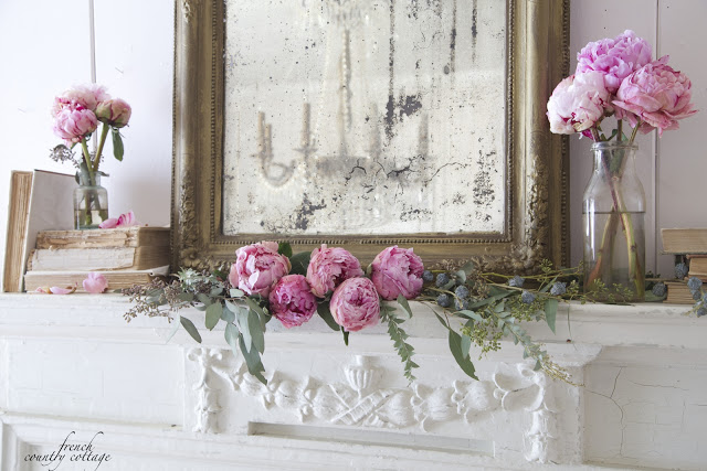 Peonies on mantel with gold mirror and old books