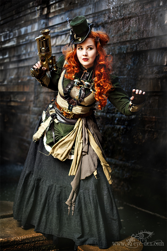 Steampunk woman with red hair wearing clothing in earth tone colors (green, brown, gray). Women's steampunk fashion and costumes