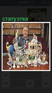 мужчина показывает статуэтку кареты и различных персонажей рядом