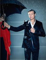 Yağmurda ıslanırken şemsiyesini bir bayana tutarak jest yapan bir adam