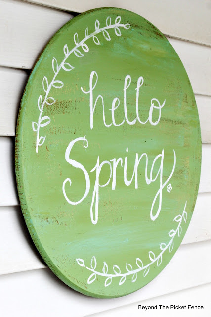 hello spring sign hand painted on an old table top