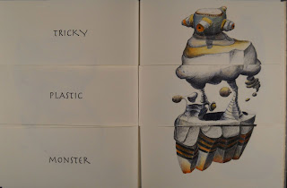 "An open book. The lefthand page shows the text ""Tricky Plastic Monster"" and the right shows a rocky, striped creature."