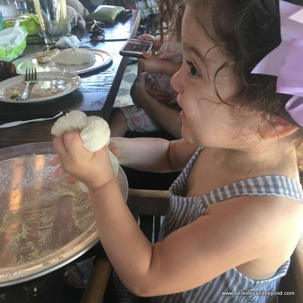 child playing with pizza dough at Dough Pizzeria Napoletana at Hemisfair in San Antonio, Texas