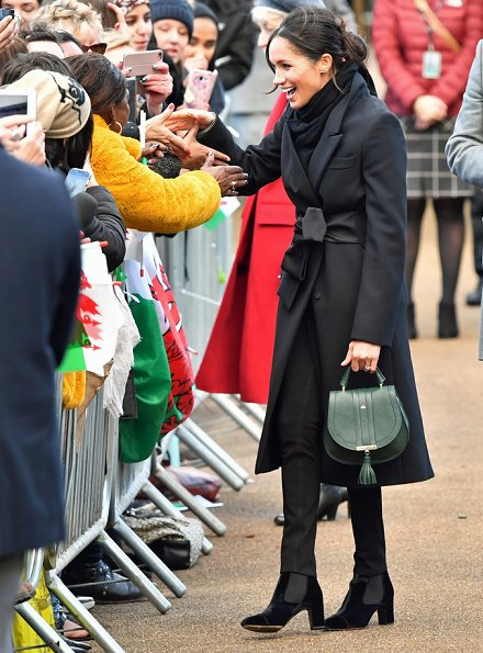 Meghan Markle carried Demellier London The Mini Venice Bag, Meghan Markle wore Tabitha Simmons Kiki boots, wore Theory wool jacket. wedding dress at ceremony