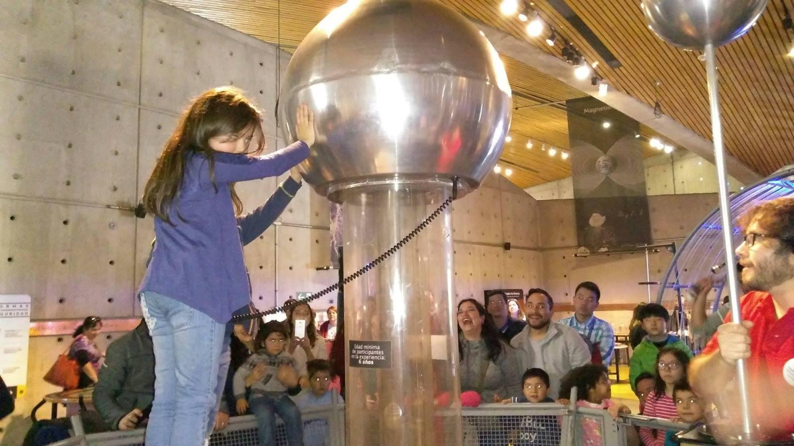 Garota testa experiência de eletromagnetismo