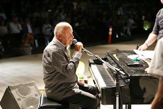 Ο Μίμης Πλέσσας μιλάει ενώ κάθεται στο πιάνο