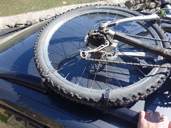 detalle de sujeción de la rueda. bici encima del coche sin portabicis, solo con las barras longitudinales