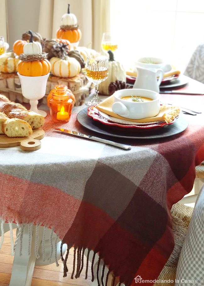 Fall table with bread on wooden board and pumpkin centerpiece