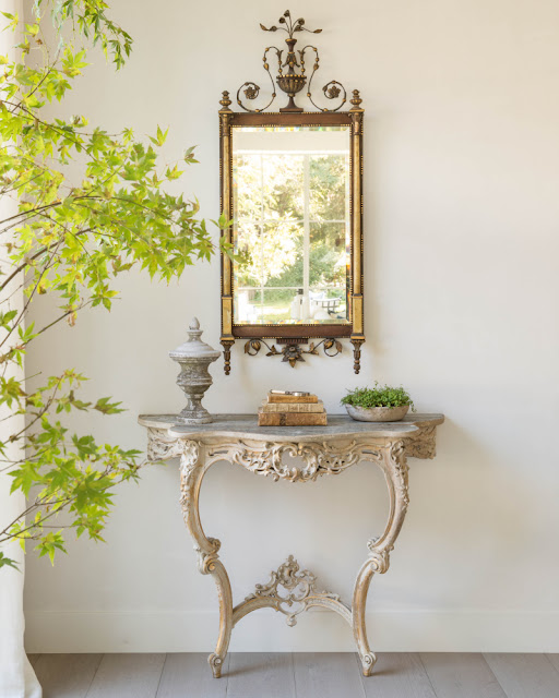 Antique entry table with gilded mirror in modern farmhouse foyer by Giannetti