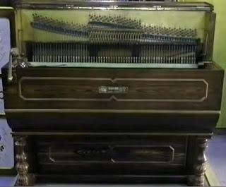 Organillo grande, del tamaño de un piano. A la izquierda del mueble la manivela que al girar mueve el rodillo. Tiene la tapa abierta y deja ver las cuerdas.