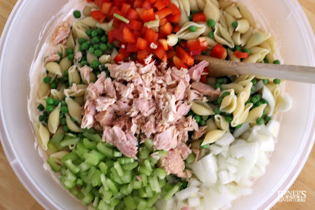 Ingredients for creamy tuna pasta salad in bowl with spoon ready to be mixed