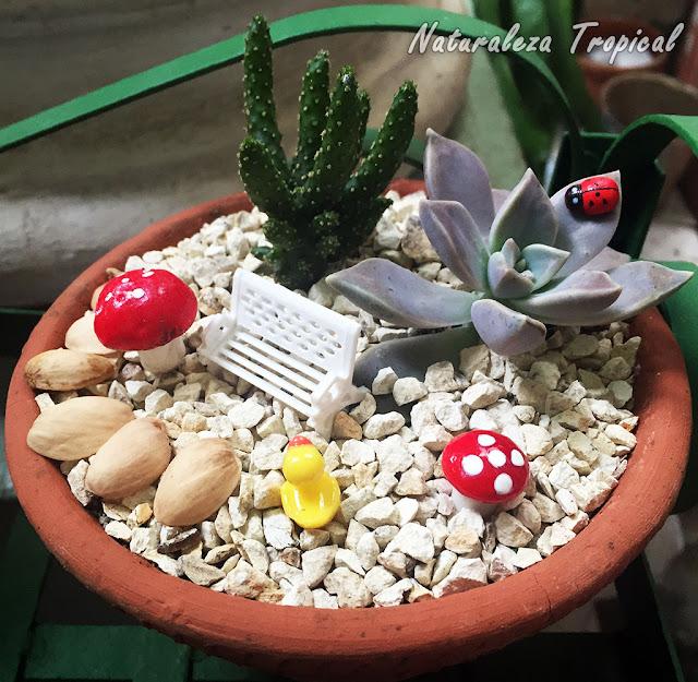 Mariquita artificial sobre planta suculenta, banco en miniatura y algunos hongos artificiales