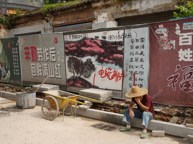 construction worker sitting down on the side of the road and talking on a mobile phone in Nanping, Zhuhai