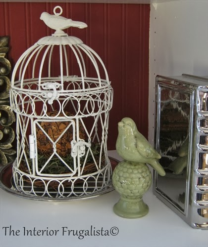 Silver round plate used as a base for a vintage bird cage