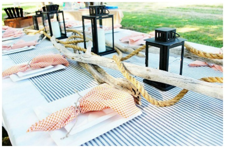 Coastal table setting with striped table cloth and lanterns