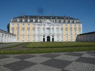 Ein großes, Gelbweißes Barrockschloss, vordem sich eine grüne Wiese erstreckt. Im Hintergrund ein strahlend blauer Himmel