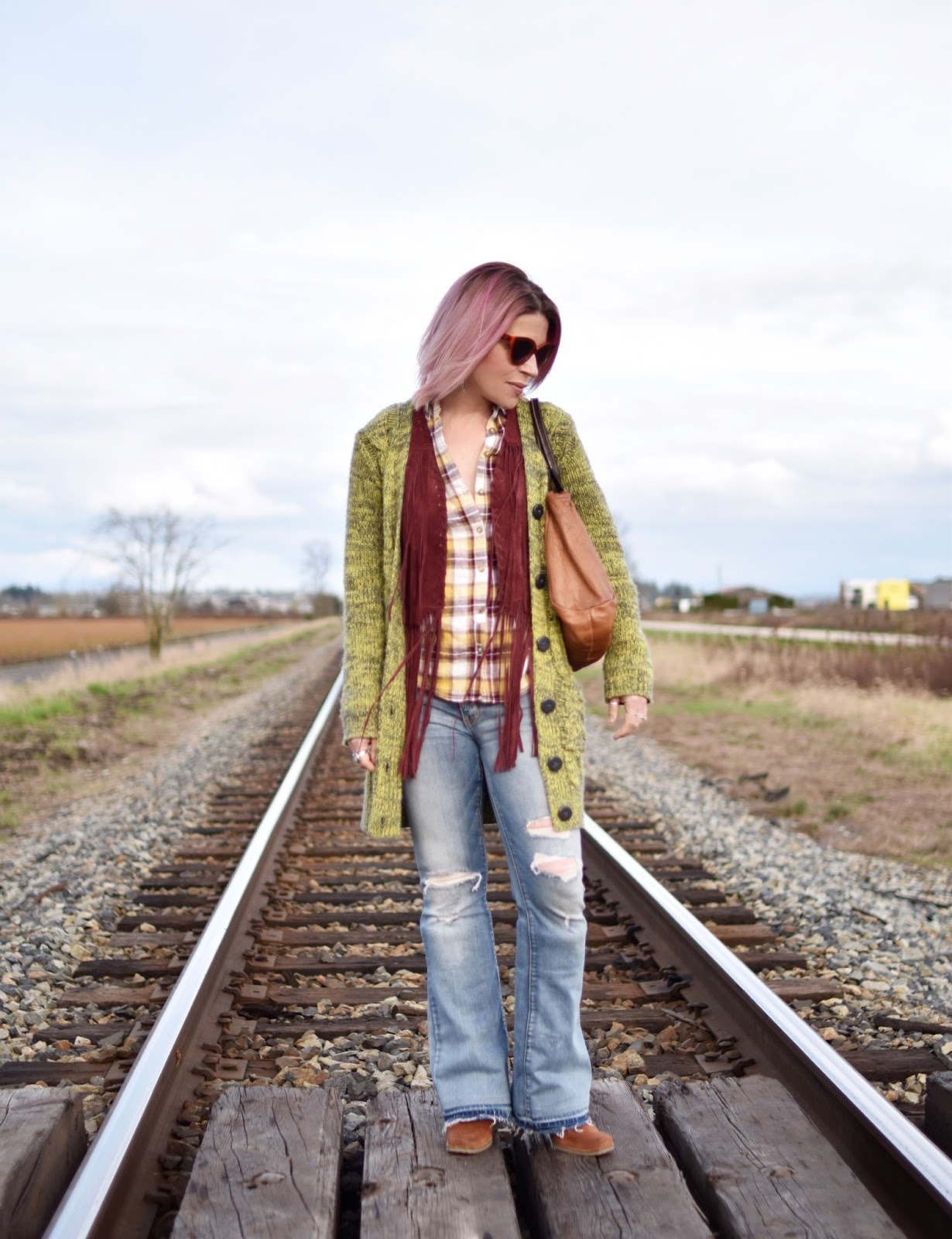 Monika Faulkner outfit inspiration - styling a plaid shirt, fringy vest, distressed flare jeans, and grandpa cardigan