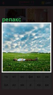 мужчина лежит на траве лицом к небу, происходит релакс