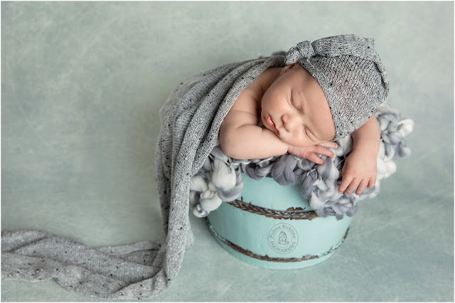 Baby boy is posed in a sage bucket