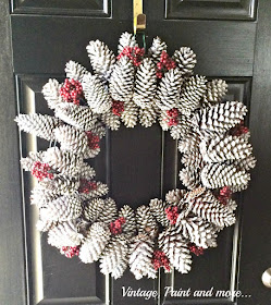 Vintage, Paint and more... This is a gorgeous pine cone wreath diy'd with found pine cones, spray painted white and sprinkled with snow glitter and red berries.  Perfect for your front door through the whole winter.