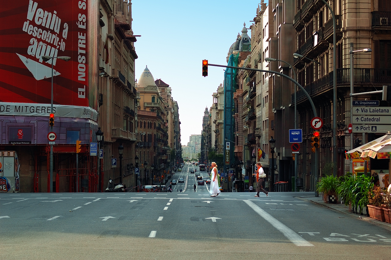 Woman in white crossing Via Layetana street in BArcelona