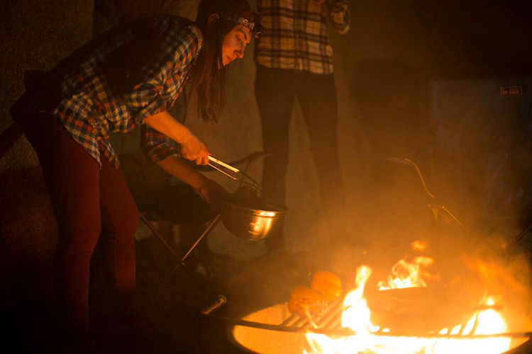 Rachel cooking over a campfire