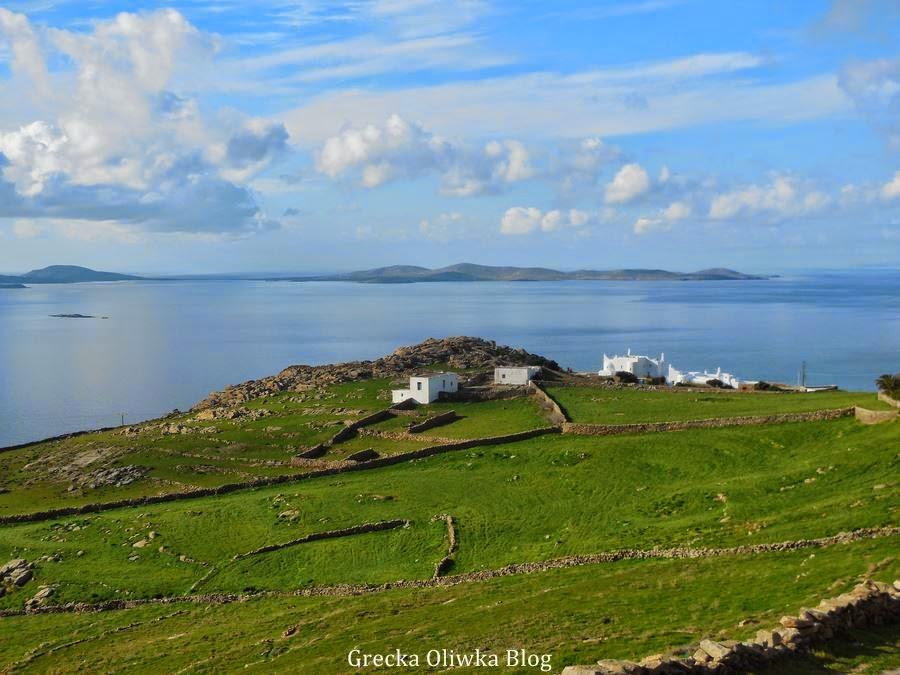 biały domek na zielonym wzgórzu na tle błękitu greckiego morza i nieba Grecja