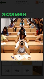 В аудитории сидят студенты за столами и сдаю экзамен. Парень схватился руками за голову, другие пишут