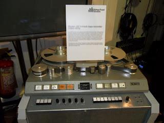 Fotografía del Struder J37, un cuatro pistas de cinta abierta. La imagen muestra el reproductor/grabacor con cinta puesta y la botonera que lo controla