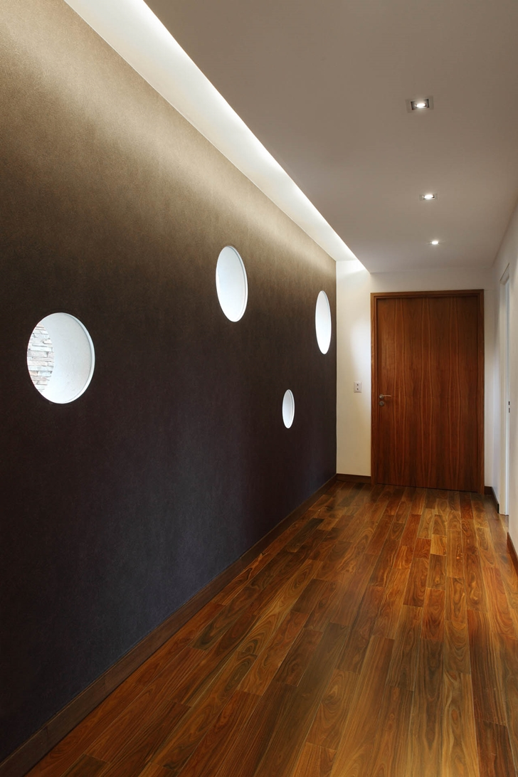 Hallway with round windows in Modern Villa Devoto by Andres Remy Architects