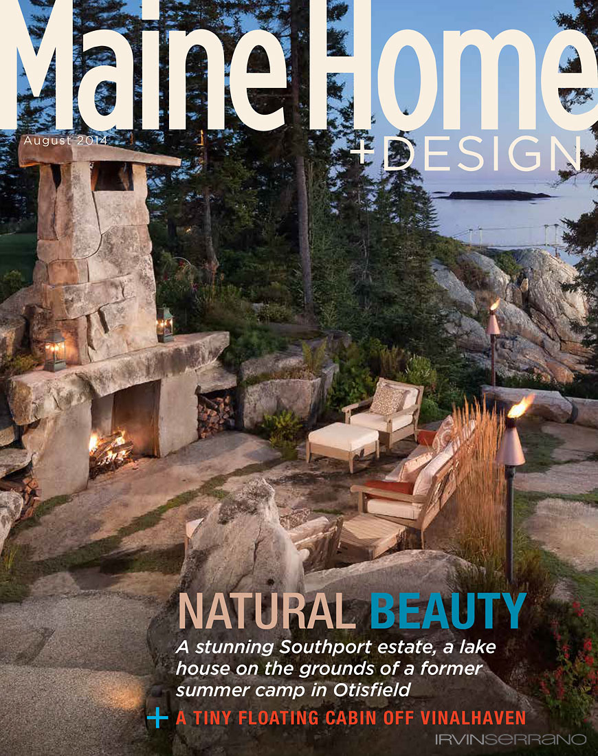 A view of an outdoor living room, with towering stone fireplace, overlooking the ocean on a stone patio graces the cover of Maine Home and Design Magazine.