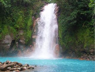 Cascada del río celeste, que baja entre la vegetación y cae varios metros a una laguna de azul celeste