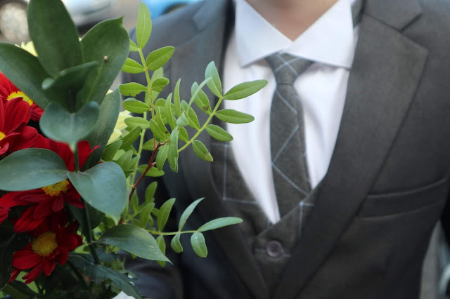 Flowers in the foreground, and a boy wearing a waistcoat and tie, with a contrasting grey jacket over the top slightly in the background.