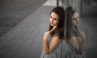 Chica apoyada en pared reflectante