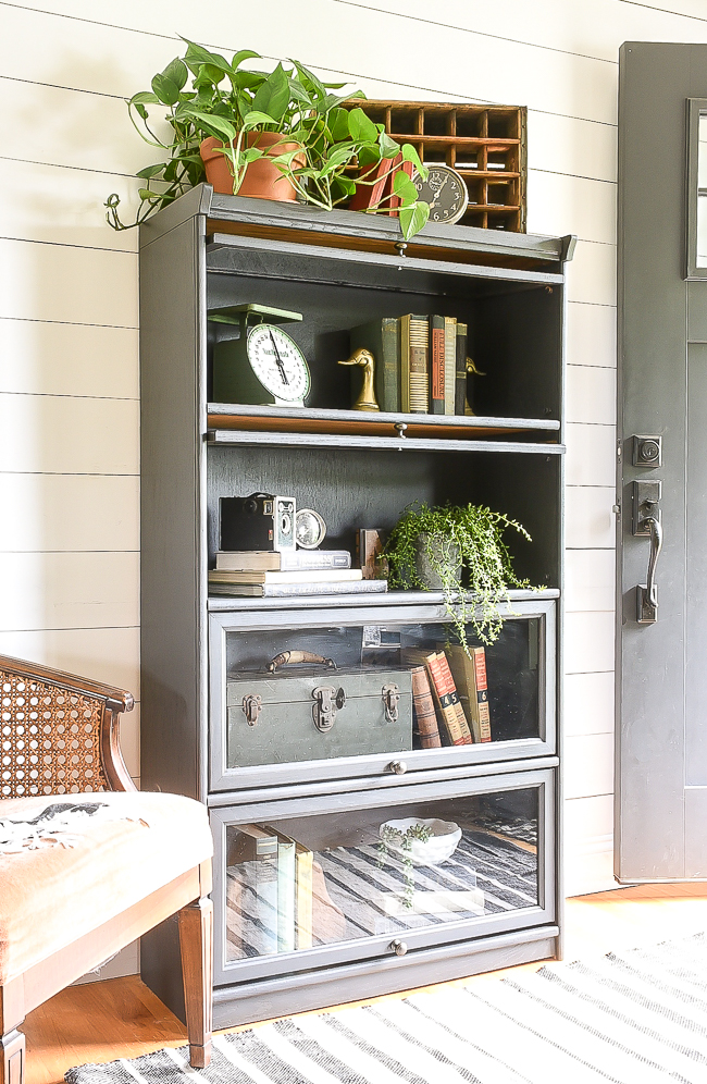Unique vintage finds styled on a painted barrister bookcase