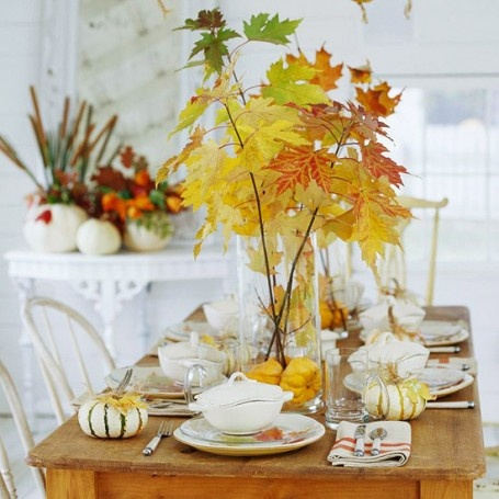This table setting featuring colorful leaves, mini pumpkins and an orange color scheme is great for fall.
