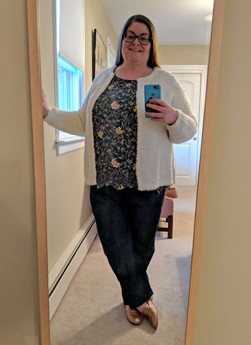 image of me standing in a full-length mirror with my hair down, wearing grey-framed glasses, a fuzzy white cardigan sweater, a floral blouse with white and yellow flowers on a dark green background, loose dark chambray pants, and iridescent pink loafers