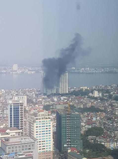 Đám cháy nhìn từ xa, xe cứu hoả chỉ vươn được tới tầng 7 của dự án