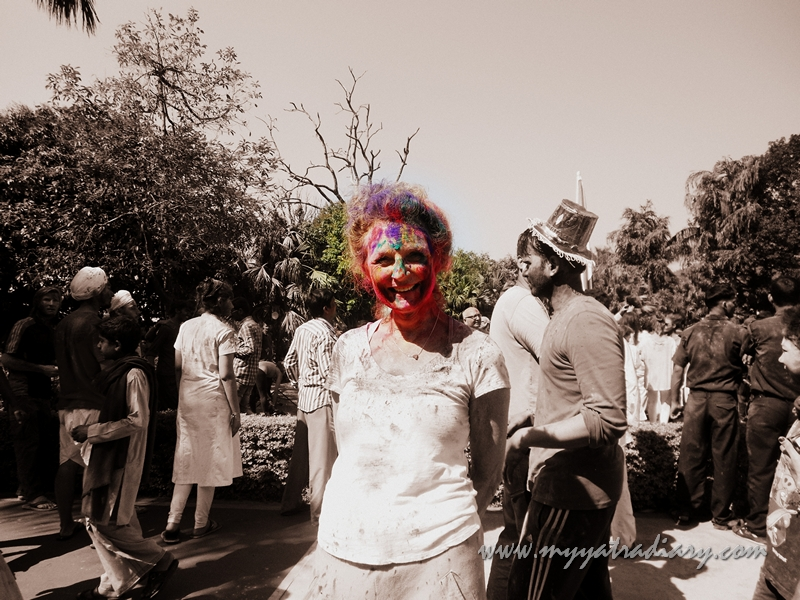 A color soaked woman poses on the festival of Holi